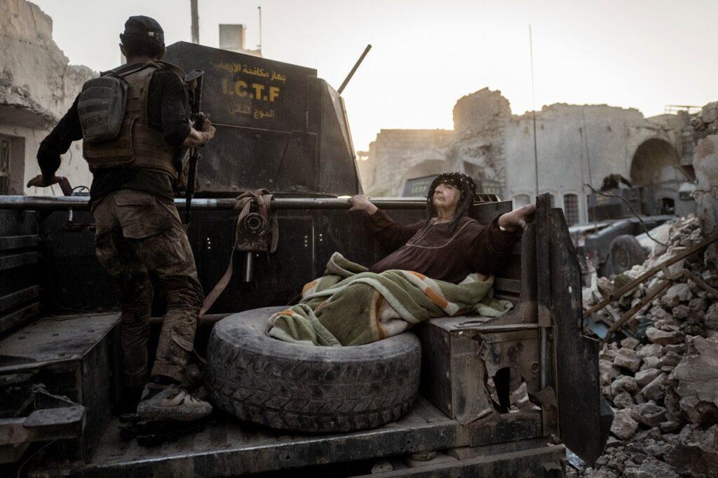 En ældre dame bliver kørt gennem byen på ladet af en af Golden Divisions pansrede biler. Temperaturen nærmer sig 50 grader, og hun er for afkræftet til selv at komme væk fra kampzonen. 11 dage senere - 10. juli 2017 - erklærer den irakiske premierminister, Haider al-Abadi, at Mosul er befriet, selvom der stadig er spredte kampe rundt omkring i gaderne. Fotograf: Rasmus Flindt Pedersen